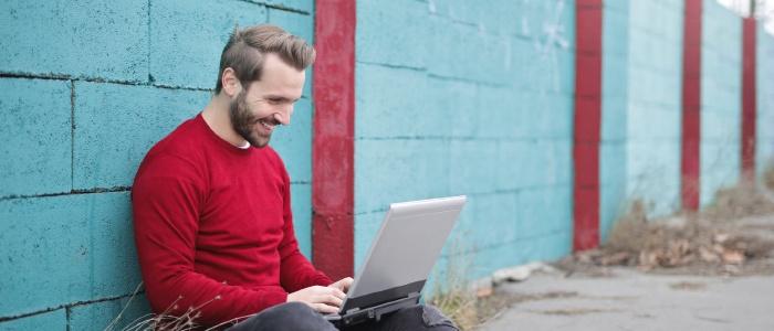 Bilden visar en man som sitter utomhus med en laptop i knät. Han sitter på marken framför en mur.
