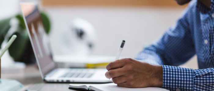 Bilden visar en man som sitter i en rutig skjorta framför en dator där han skriver anteckningar om rekryteringslösningar på ett anteckningsblock.