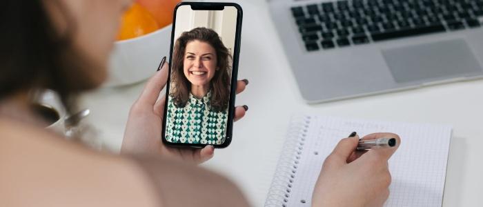 En rekryterare sitter och kollar på bild på en kandidat hon tidigare genomfört en intervju med. Rekryteraren för anteckningar på ett anteckningsblock.
