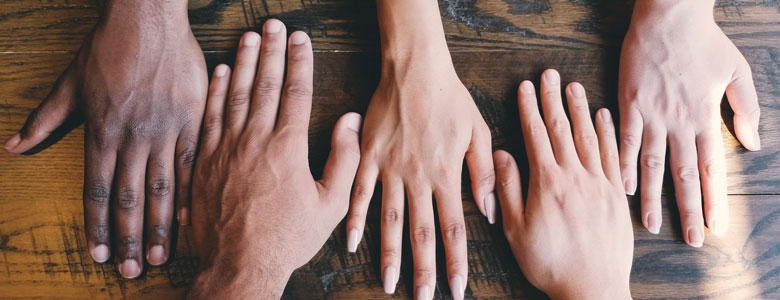 Bild på händer som visar på mångfald inom verksamheten till följd av en inkluderande rekryteringsprocess.